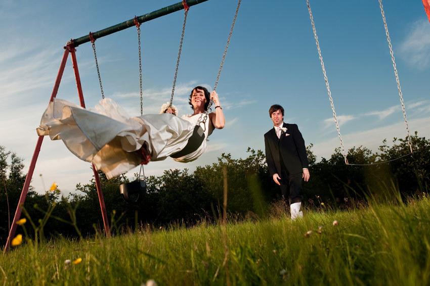Bride-swings-on-swingset-in-white-wedding-dress-groom-in-tux-pushes-her-on-swing-blue-sky.full