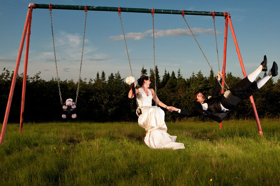 Bride and groom (in full wedding day garb) swing on swingset while holding hands