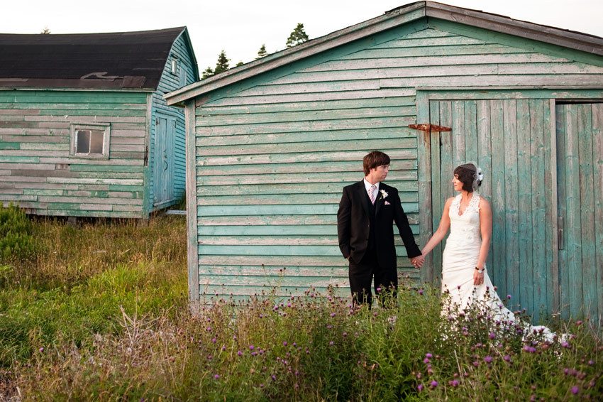 Bride in v-neck lace wedding dress, groom in black formal tux, hold hands in front of old cottage
