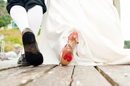 Bride wears red bridal heels with heart on sole, groom in high white socks and black patent leather