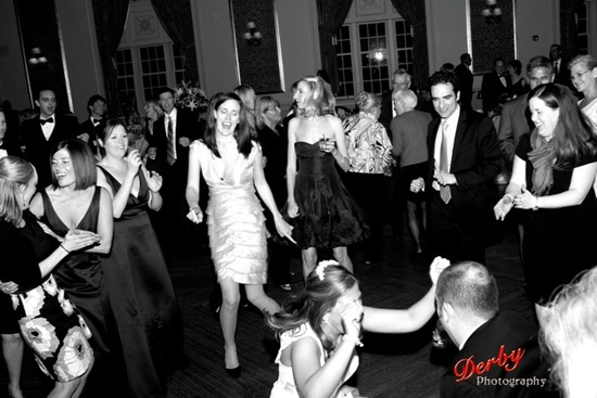 This bride and groom and their friends are having fun dancing at their wedding to a live orchestra.