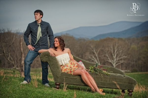 Nearlyweds pose atop Virginia hill on vintage chic chaise lounge, mountains in background