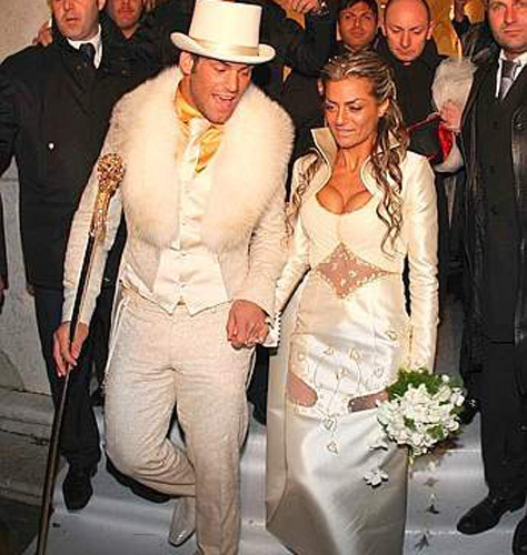 The groom's top hat and fur trimmed coat lend a special look to this wedding outfit.