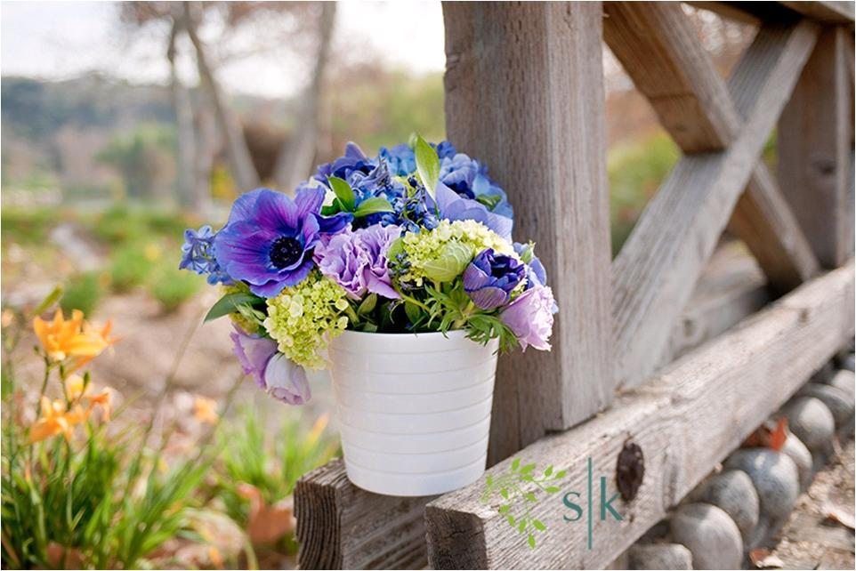 Beautiful floral arrangement for outdoor wedding ceremony- bold blue, purple and green flowers in wh