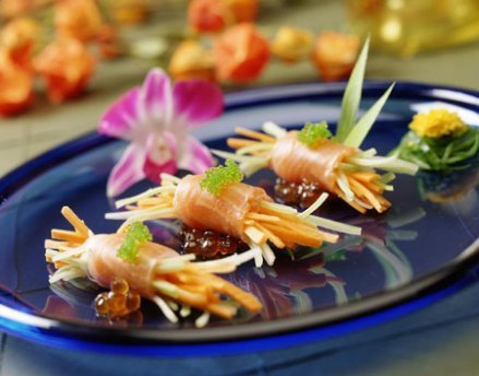 This elegant wedding meal is salmon wrapped in roe on a blue plate with a purple flower.