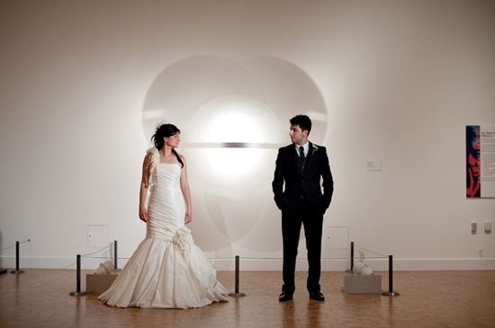 Bride in mermaid style wedding dress (with asymmetrical neckline) stands with groom in front of famo