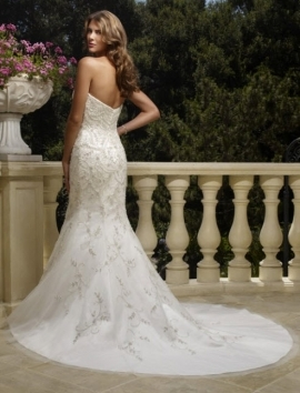 This beautiful white wedding dress features a deep cut back and a mermaid cut silhouette