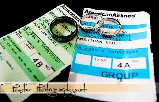 Two American Airlines plane tickets with diamond engagement ring and wedding bands on top