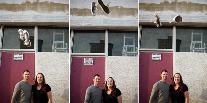 Bride and groom pose outside together in casual clothes, shoes fly up in the air