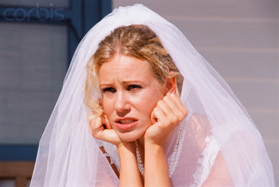 This blonde bride looks unhappy and stressed, despite her lovely full length veil.