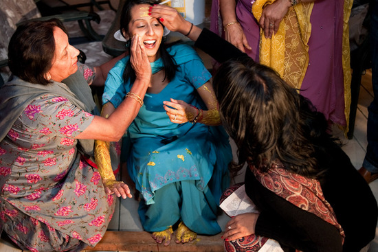 Bride in teal and gold traditional Indian sari gets smeared with turmeric paste