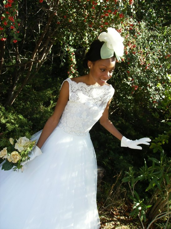 Bride wears white lace bateau neck wedding dress, vintage bridal hairpiece, and vintage kid gloves