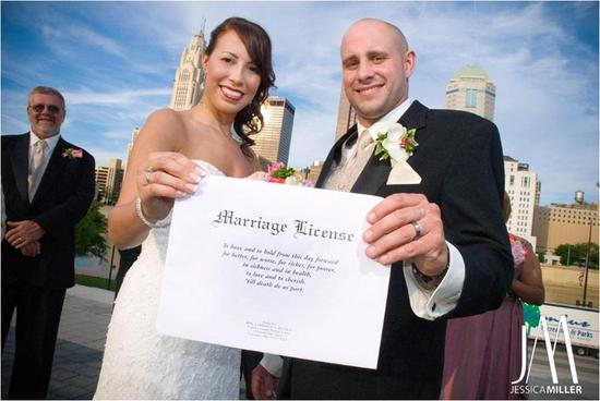 Bride and groom proudly display their marriage certificate after saying I Do