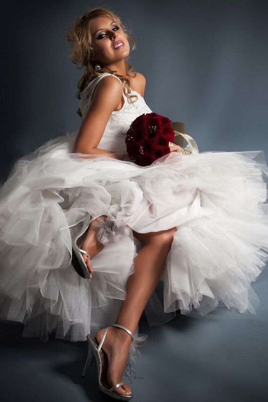 Assymentrical wedding dress (one shoulder) with full tulle skirt, bride holds dark red rose bridal b