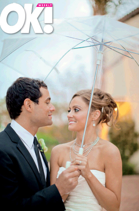 Jason Mesnick and Molly Malaney stand together under umbrella after saying I Do