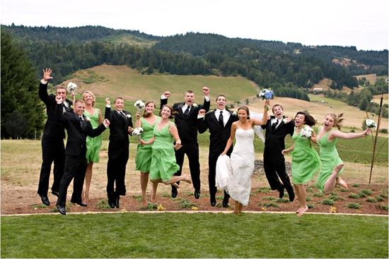 Bridal party- bridesmaids in green bridesmaids dresses, groomsmen in black suits, jump outside with