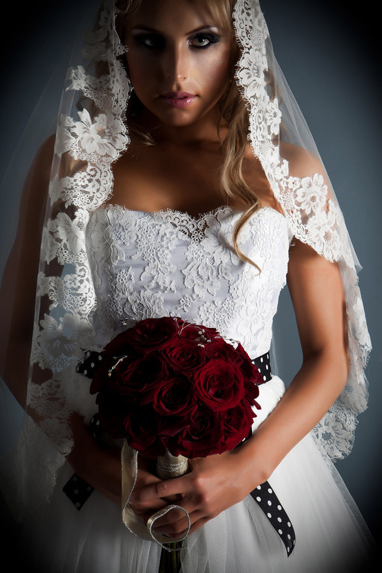Stunning white lace strapless wedding dress with black and white sash.  Bride holds deep red bridal