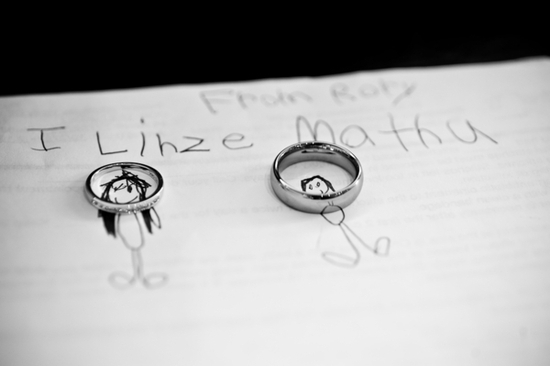 Artistic black and white wedding photo- platinum wedding bands sit on top notebook paper with stick