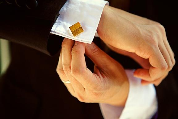 This groom is adjusting his beautiful gold cufflinks on his white shirt with black suit.