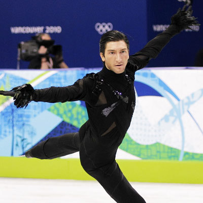 Evan Lysacek skates in a black sequined Vera Wang costume with feathered cuffs
