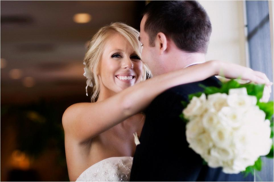 Adorable-smiling-bride-in-strapless-ivory-beaded-wedding-dress-ivory-rose-bridal-bouquet-holds-groom.full