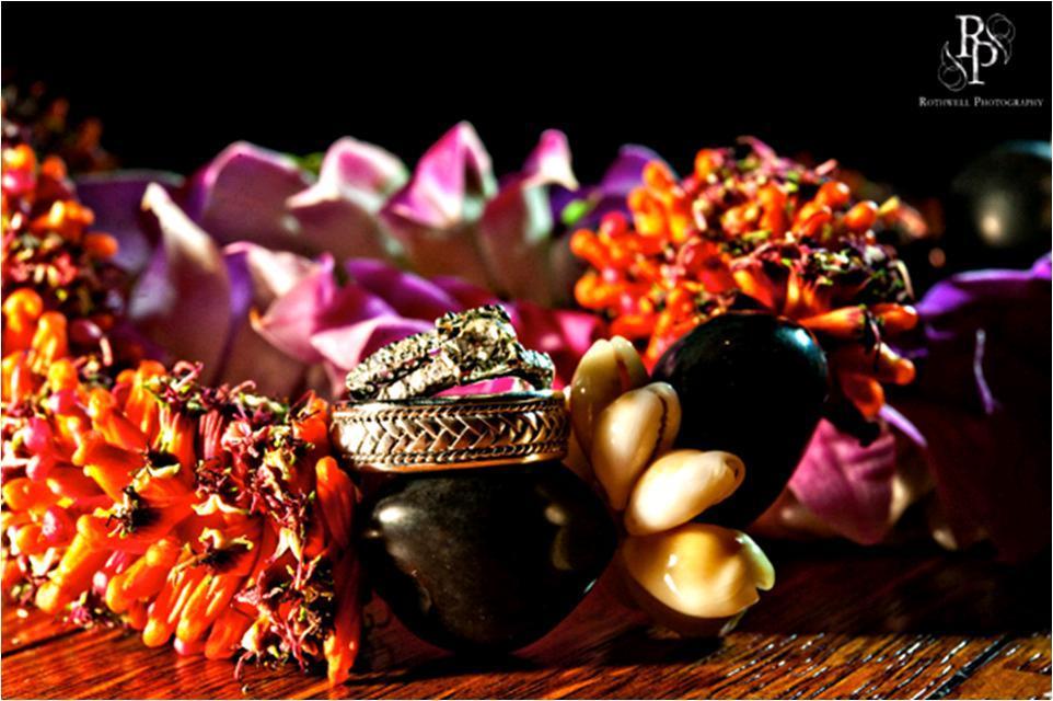 Stunning-wedding-detail-shot-puca-shells-orange-purple-hawaiian-flowers-diamond-engagement-rings-wedding-bands.full