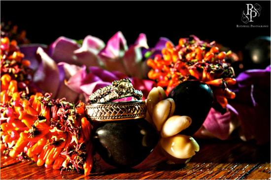 Beautiful vibrant purple and red orchids and other Hawaiian flowers, beneath diamond engagement ring
