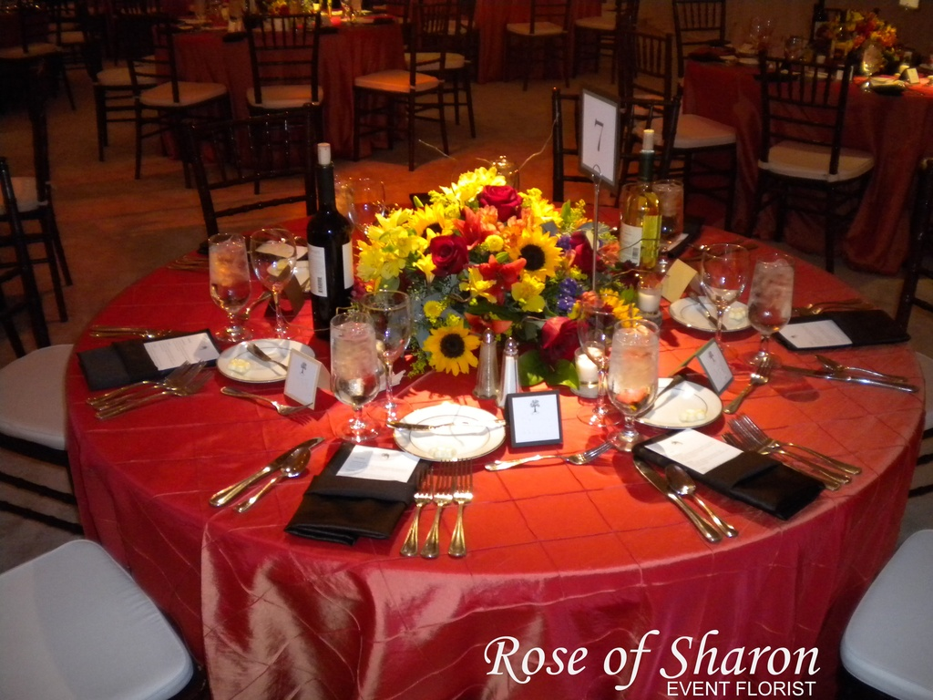 These wildflower centerpieces use a yellow and red palette on a red tablecloth.