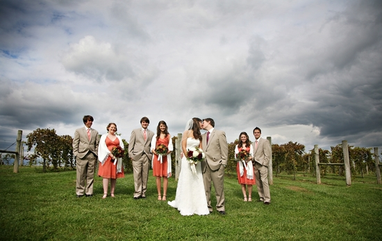 Wedding party, bride and groom pose outside in open vineyard, cloudy blue sky as backdrop