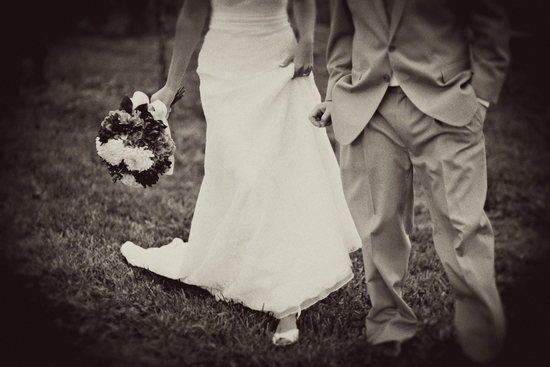 Wedding photo of bride in white wedding dress, groom in taupe morning suit, hand in hand