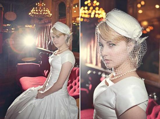 The pillbox hat with a birdcage veil and the bride's modest wedding dress all add a feeling of vinta