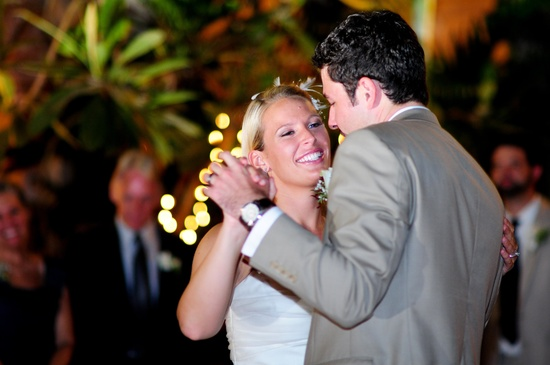 This blonde bride in a white sleeveless dress is dancing with her groom in a grey suit.
