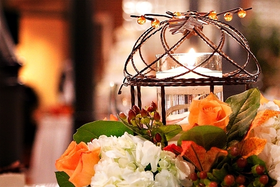 Gorgeous orange, peach, ivory and green floral centerpiece arranged around hurrican vase and candle