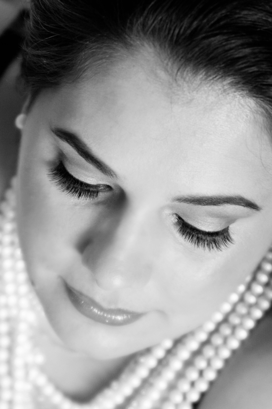 Beautiful bride wears pearls around neck, perfect bridal makeup complimented with fake eyelashes