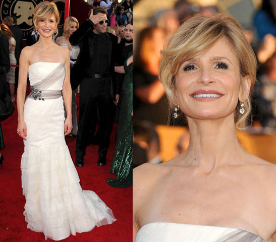 Kyra Sedgwick in a white Vera Wang dress with sheer grey bands and jeweled brooch