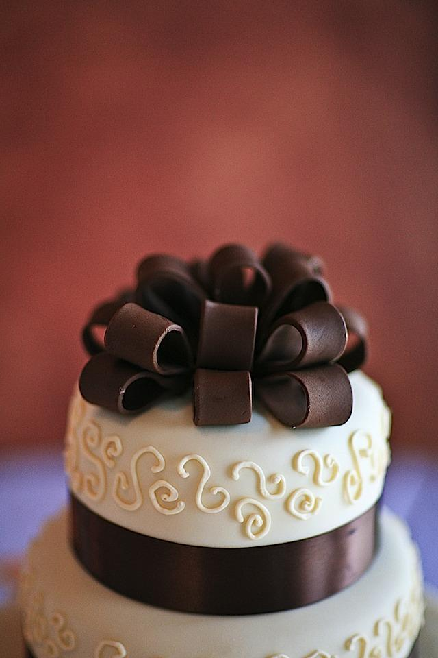 Beautiful ivory fondant wedding cake with chocolate brown ribbon on top