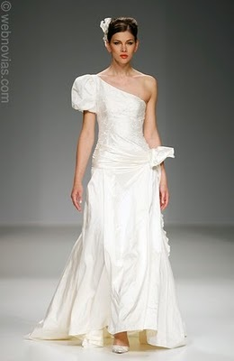 This white satin wedding dress has an asymmetrical neckline with one large sleeve, and a hip area be