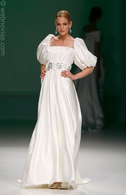 This loose fitting white wedding dress features a studded belt, empire waist, square neckline, puffy