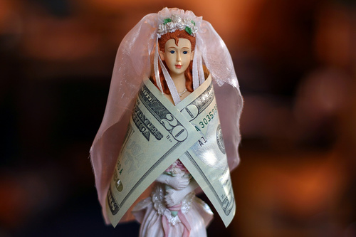 This bride doll is wrapped in a twenty dollar bill to show the idea of a rich bride bringing money t