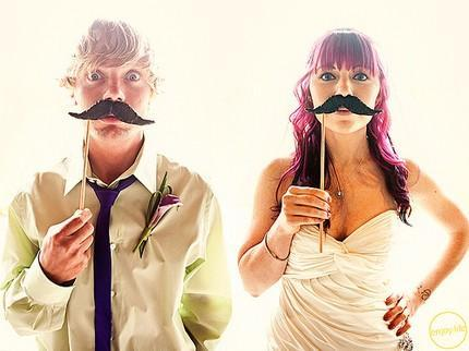 Funky bride and groom pose artistically, hold up mustaches on sticks