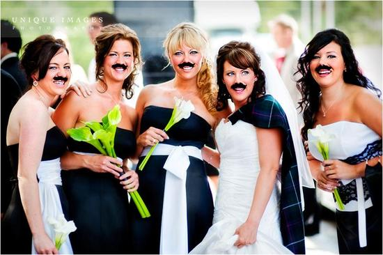 Bridesmaids in black and white bridemaids' dresses pose with bride, all wear fun mustache