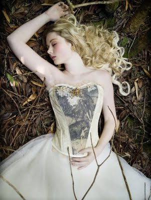 Like out of a fairytale, whimsical bride lays on ground in ivory wedding dress and flowing curls
