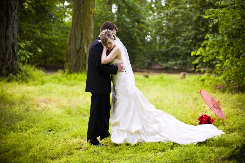 Bride In Ivory Wedding Dress Poses With Groom In Whimsical Forest