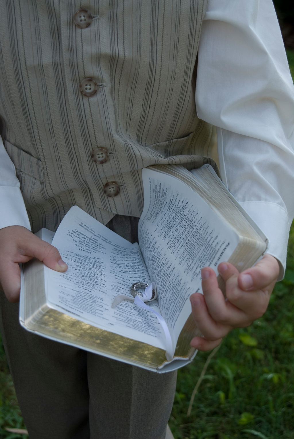 The ring bearer carries the wedding bands inside a family bible.