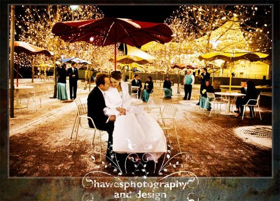 Bride in white fur stole sits on grooms lap, outdoor at winter wedding surrounded by twinkling light