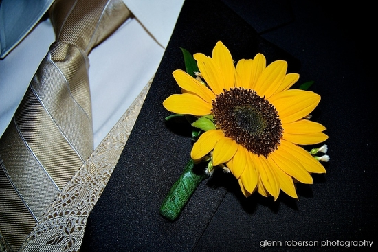 Groom in black tux, white shirt, cream and gold metallic stiped tie, yellow daisy on lapel