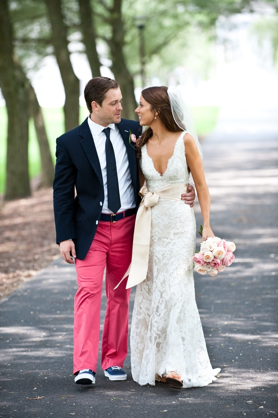 Bride in v-neck lace wedding dress walks with groom, outfitted in red Bonobos pants and dark navy ja
