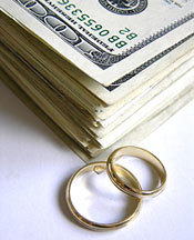 These gold wedding rings and pile of money represent money spent on your wedding.
