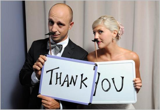 Bride and groom have fun posing with fake mustaches, hold Thank You signs