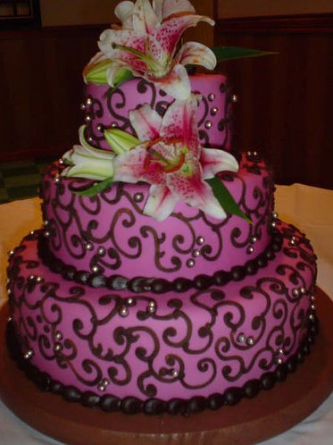 This three-tiered purple wedding cake with brown icing and pink ...